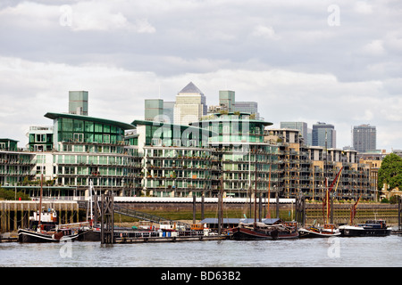 Typical private Thames riverside apartments Wapping East End London England UK, with Canary Wharf in the background - Stock Photo