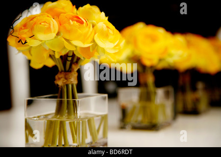 A row of three yellow faux flower bouquets set in gel water on a table - Stock Photo