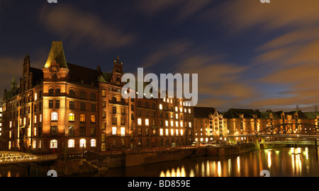 The historic warehouse district of Hamburg, northern Germany under a cloudy sky at the blue hour on Saturday February - Stock Photo