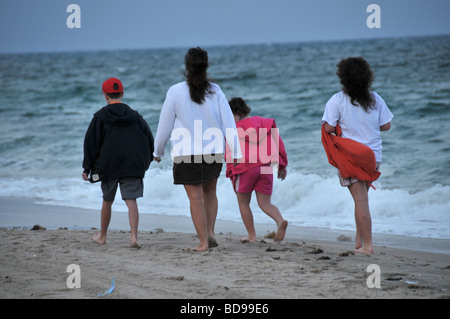 A young family walks on the beach in Florida. - Stock Photo
