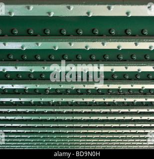 Lines of rivets in steel girders on underside of railway bridge over river close up - Stock Photo