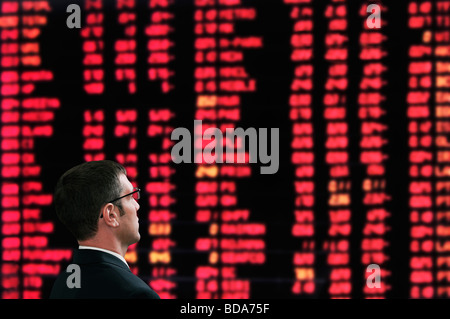 Stockbroker in Front of a Screen Showing Market Prices in a Stock Exchange - Stock Photo