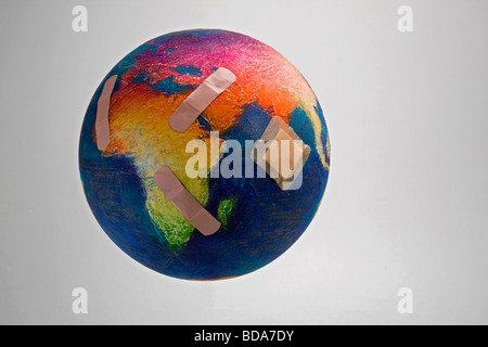 Still shot of a world globe with band aids on Africa and Asia - Stock Photo