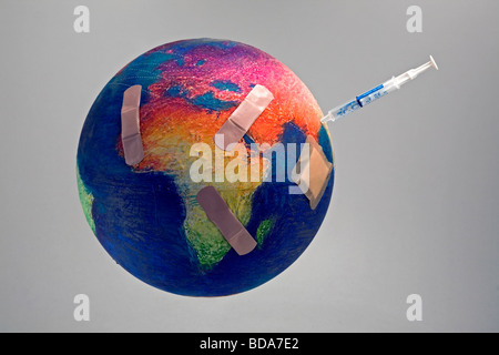 Still shot of a world globe with band aids on Africa and a syringe on Asia - Stock Photo