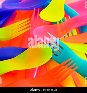 Brightly coloured plastic cutlery. - Stock Photo