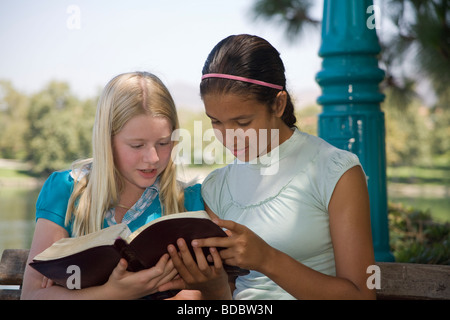 two 2 girls reading Racially mixed Ethnic diversity Hispanic Caucasian discuss Bible nature natural young person - Stock Photo