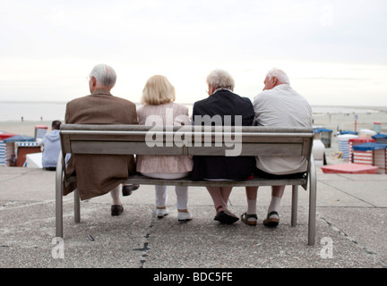Pensioneers sittin on a bench at the Northsea - Stock Photo