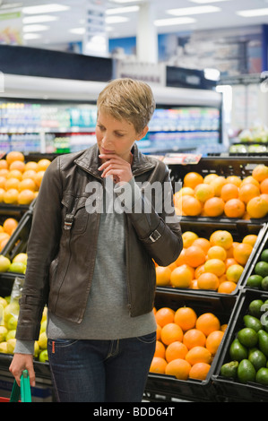 Woman buying fruits in a supermarket - Stock Photo