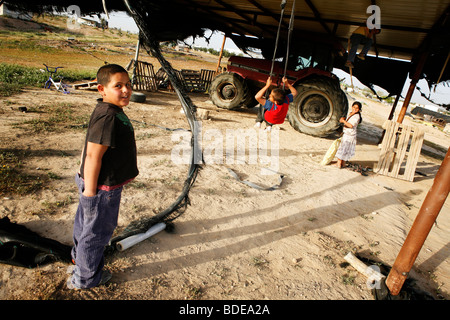 Children play on an improvised swing in the unrecognized Bedouin village of Al Araqeeb in the Negev desert, Israel - Stock Photo