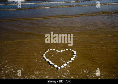 A heart in the sand made from white chalk stones on Bridlington's North Beach. The incoming tide threatens to submerge - Stock Photo