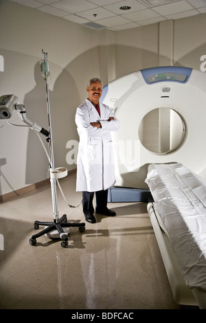 African American radiologist next to CT scanner - Stock Photo
