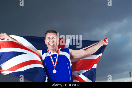 athlete cheering with U.K. flag and medal - Stock Photo