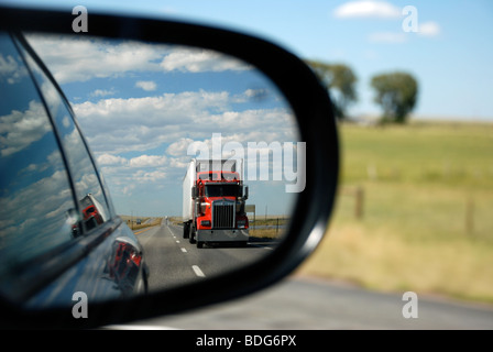 Truck in rear view mirror - Stock Photo