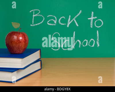 Back to school written on a chalkboard with an apple over books. - Stock Photo