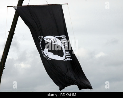 POW MIA flag hanging from a crane high in the sky. The sky is overcast. - Stock Photo