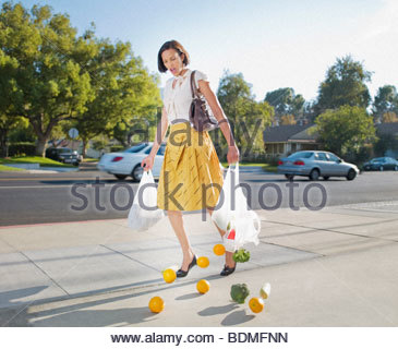 Woman dropping groceries on sidewalk - Stock Photo