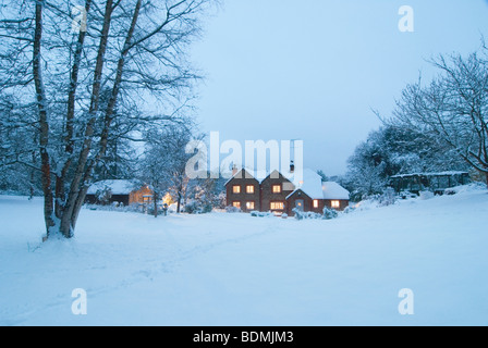 Christmas card image of winter landscape with cosy cottage in virgin snow with silver birch tree in the evening - Stock Photo