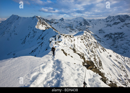 Secured climber on a fixed rope route in the high mountains in winter, Arlberg, Verwallgruppe mountain range, North - Stock Photo