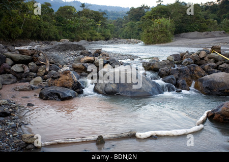 Absorbent boom places accross an Amazonian river during the cleanup process of an oil spill. - Stock Photo