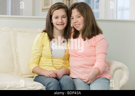 Two teenage girls sitting together - Stock Photo