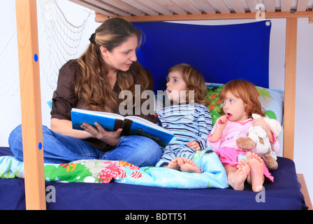 mother reading a book to her children in a Billi-Bolli loft bed - Stock Photo