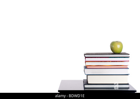 Horizontal image of a stack of books with a green apple on white - Stock Photo