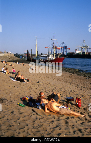 People at the beach of the Elbe river, in the back the historic ship museum Oevelgoenne, Elbe riverr and port of - Stock Photo
