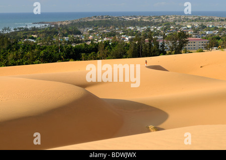 Sand dunes and structures in front of the city of Mui Ne, Red Sand Dunes, Vietnam, Asia - Stock Photo