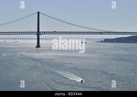Ponte 25 de Abril, suspension bridge over the Tagus River, and a speedboat, Lisbon, Portugal, Europe - Stock Photo