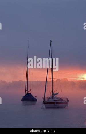 Sun rising behind sailing boats and fog over Ammersee lake, Bavaria, Germany, Europe - Stock Photo