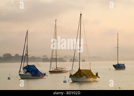 The first light of the day hits sailing boats in front of thick morning fog at Ammersee lake near Schondorf, Bavaria, - Stock Photo