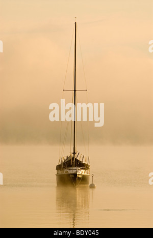 Sailing boat and fog at the southern end of Ammersee lake in Diessen, Bavaria, Germany, Europe - Stock Photo
