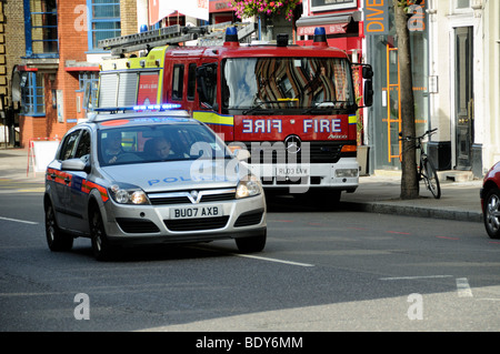 Police car with flashing lights passing fire engine, Upper Street Islington London England UK - Stock Photo