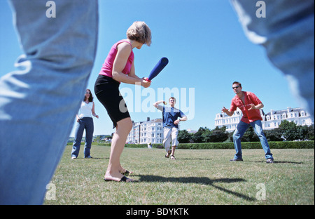 A group playing baseball in a park - Stock Photo