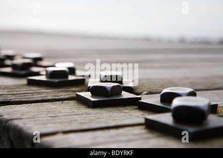 A line of nuts and bolts holding together a wooden jetty. - Stock Photo