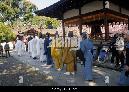 Shinto priests proceed to worship, shrine festival during the cherry blossom at the Hirano Shrine, Kyoto, Japan, - Stock Photo