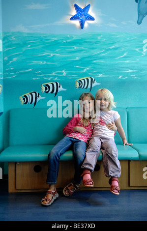 Two girls, sisters, on a bench in front of a painted wall - Stock Photo