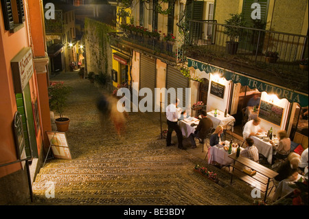 Customers enjoy dinner at an outdoor cafe in Bellagio, Italy. - Stock Photo