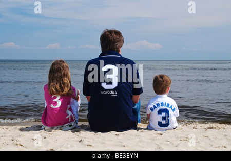Father and children sitting on the beach, looking at the Baltic Sea, boy, 2 years old, girl, 7 years old, Heringsdorf - Stock Photo