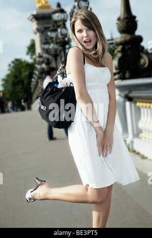 Portrait of a young dark blonde woman in a white dress with a handbag standing on one leg, Alexander Bridge, Paris, - Stock Photo