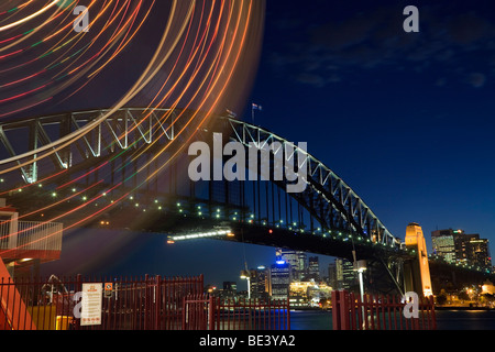 Light trails of the Luna Park ferris wheel with the Harbour Bridge in the background. Sydney, New South Wales, AUSTRALIA - Stock Photo