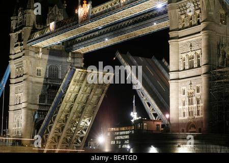 Lift bridge opened at night to let shipping traffic pass, Tower Bridge, St. Katherine's Way, London, England, United - Stock Photo
