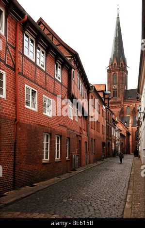 Alley with historic buildings, St. John's Church in the back, brick Gothic, Lueneburg, Lower Saxony, Germany, Europe - Stock Photo
