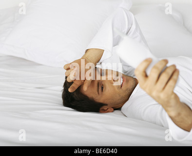 Man lying in bed, dialing cordless phone - Stock Photo