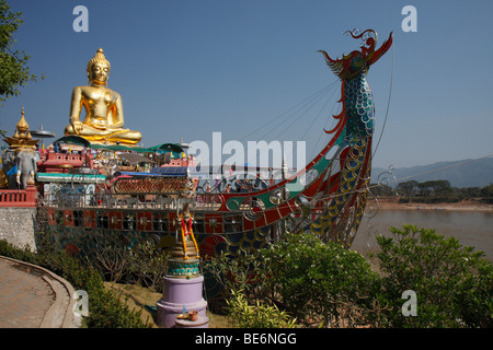 Golden statue of Buddha and stylized steel boat on the Mekong River, Golden Triangle between Thailand, Myanmar and - Stock Photo
