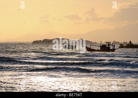 Fishing boats at sunset in the bay of Ke Ga, Vietnam, Asia - Stock Photo