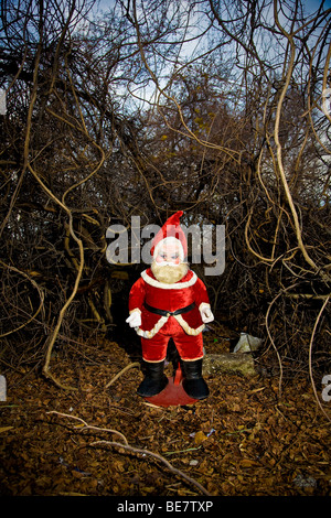 A 1960's era stuffed Santa Claus stands outdoors in a tangle of brush and overgrowth - Stock Photo