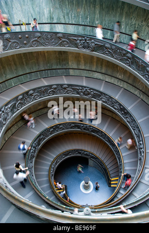 ITALY Lazio Rome Vatican City Museum Tourists walking down the Spiral Ramp exit designed in 1932 by Giuseppe Momo - Stock Photo