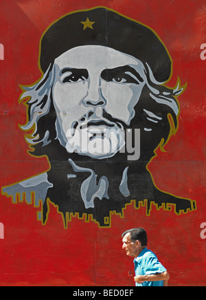 A man passes a painting of former revolutionizer revolutioniser Che Guevara in Havanna, Cuba, pictured on March - Stock Photo
