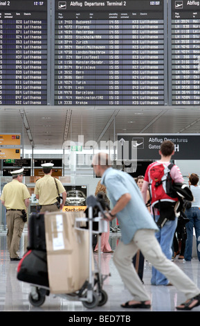 Passengers in front of the information board listing the departure times, Terminal 2 of Munich Airport, Franz-Josef - Stock Photo